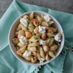 Creamy bay scallop pasta in a bowl on a teal napkin with bead detailing