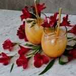 Bahamas rum punch decorated with tropical, red flowers.