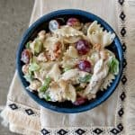 Poppy seed chicken and grape pasta salad in a blue bowl.