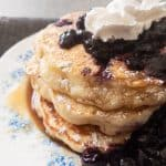 A side profile of a stack of three pancakes covered in toppings.