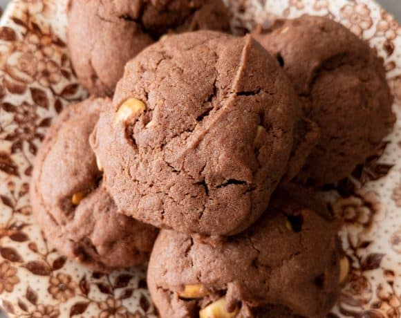 A stack of toasted hazelnut chocolate cookies on a brown floral plate.