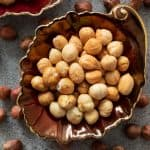 Toasted hazelnuts in a brown dish, surrounded by raw hazelnuts.