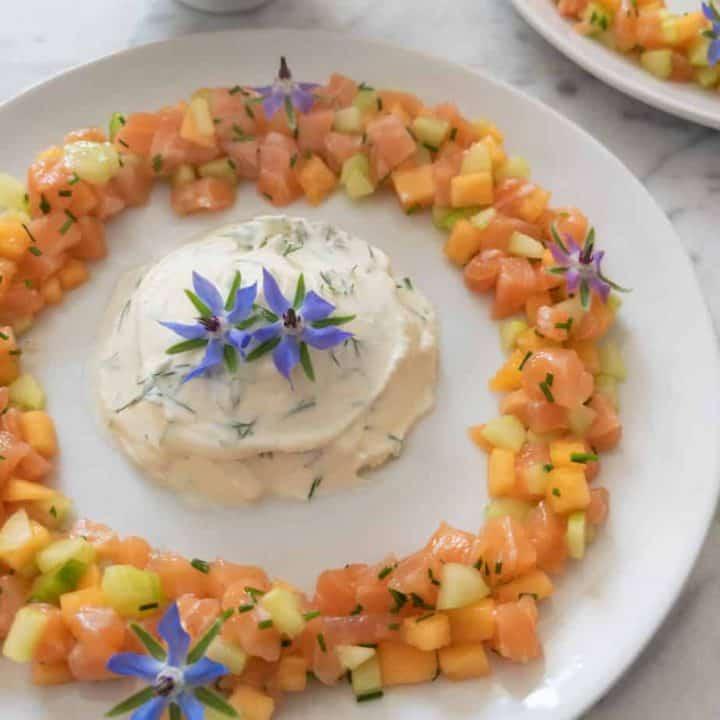 Summer melon salmon tartare with lemon mascarpone, garnished with edible borage flowers.