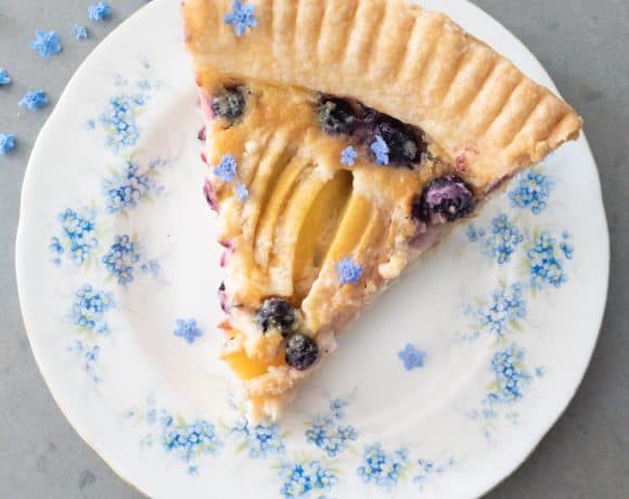 A slice of berry peach pie on a floral forget-me-not plate.
