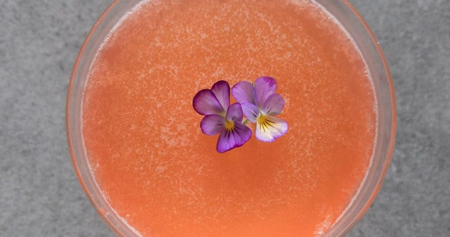 Naked and famous cocktail in a coupe glass garnished with violets.