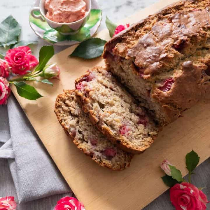 A sliced loaf of strawberry banana bread on a cutting board, surrounded by roses.