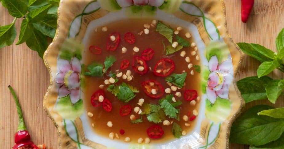 A lotus decorated bowl of prik nam pla beside lime wedges and sliced chilis.