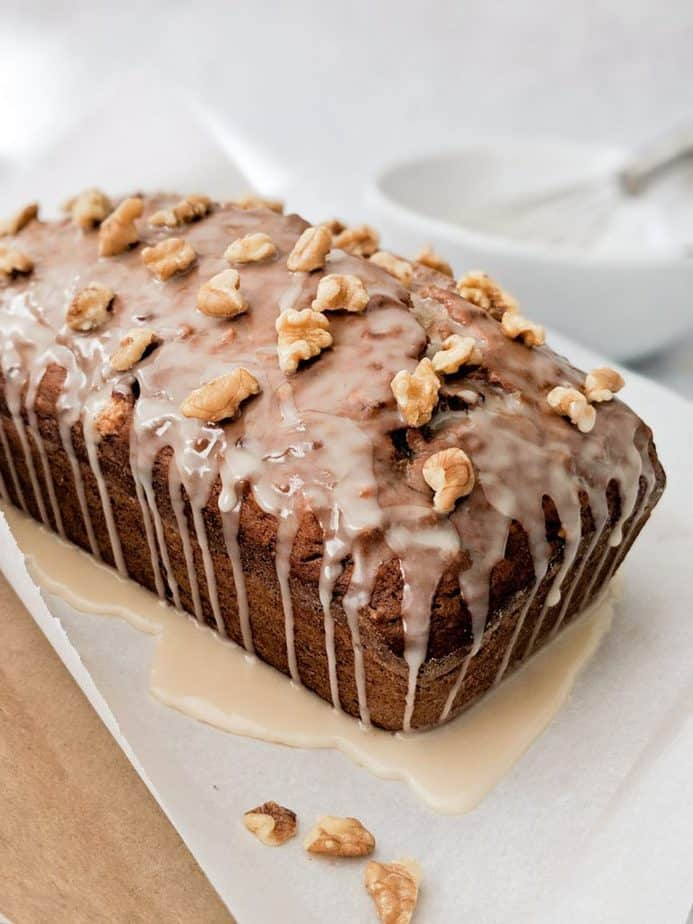 Banana bread loaf covered with walnuts and dripping with glaze