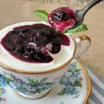 A spoon scooping blueberry vanilla compote out of a teacup.