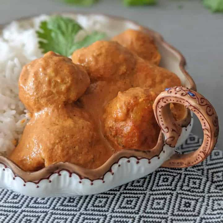 A close up of butter chicken meatballs in a decorative serving dish.