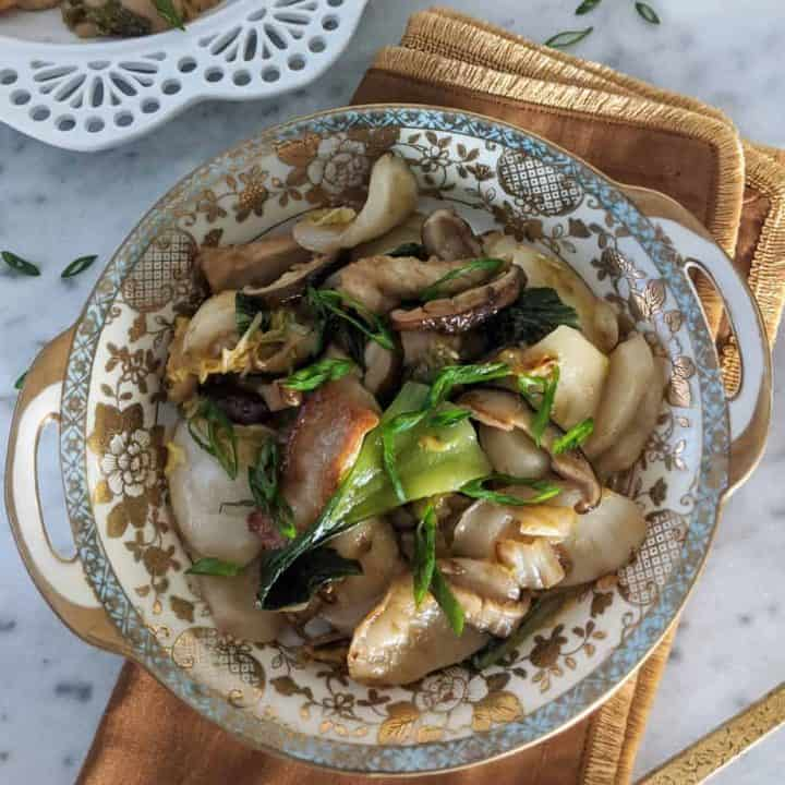 Chao nian gao in a gold-trimmed bowl, garnished with green onion.