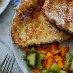 A close up of coconut french toast served with kiwi and mango.