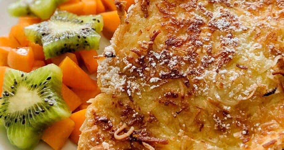 Coconut French toast served with powdered sugar, maple syrup, and fresh fruit.