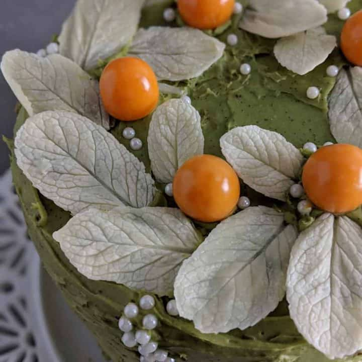 White chocolate leaves and golden berries decorate a green frosted cake.