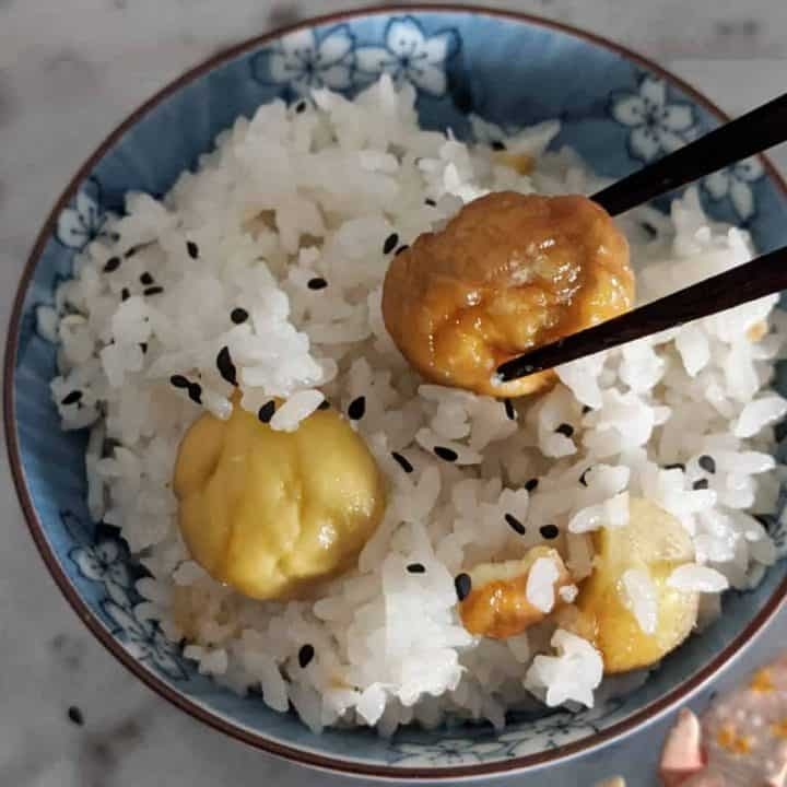 Chopsticks pulling a chestnut out of a bowl of Japanese chestnut rice.