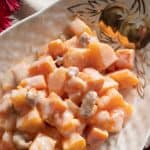 Japanese sweet potato and persimmon salad in a white serving dish.