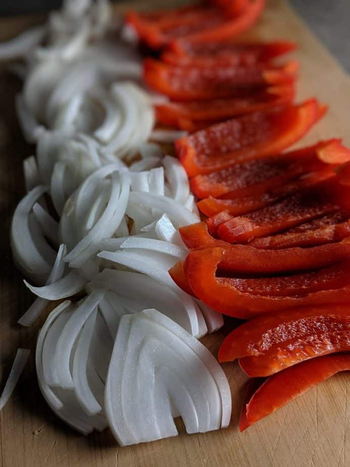 Sliced onion and red bell pepper on a cutting board
