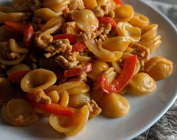 Korean spiced orecciette pasta on a white plate and frilled grey napkin