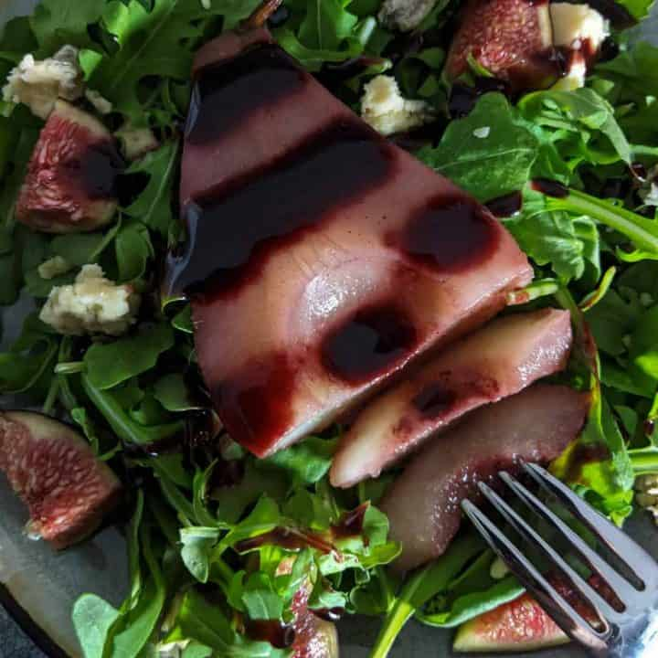 A fork cutting into a poached pear on a salad.