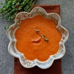 A bowl of roasted red pepper sauce with sprigs of fresh thyme.