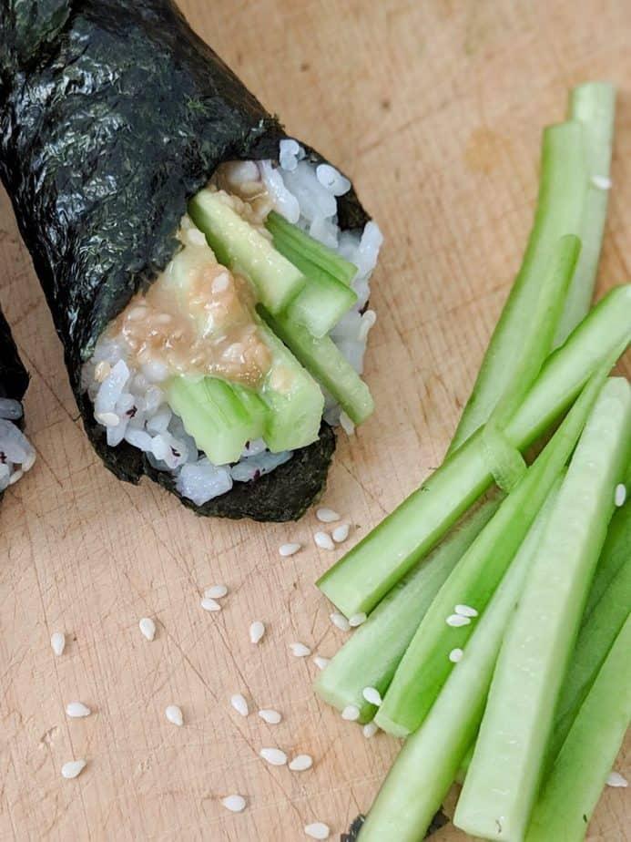 A sesame cucumber roll beside cucumber strips and sesame seeds