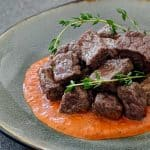 Steak bites stacked on a pool of roasted red pepper sauce, and garnished with fresh thyme.