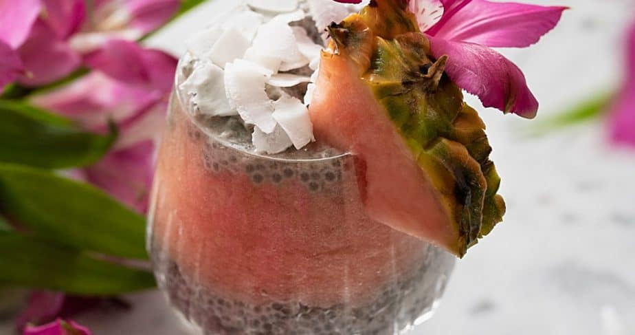 A pineapple coconut chia pudding decorated with pink pineapple, flowers, and coconut flakes.