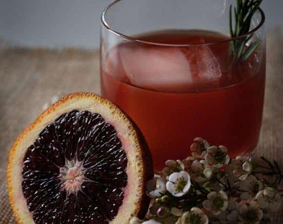 A slice of blood orange and white flowers next to a cocktail.