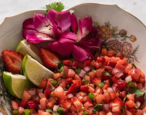 Strawberry pineapple salsa in a bowl with lime wedges and tropical flowers.