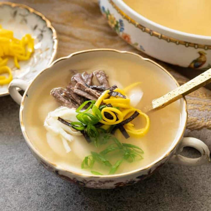 A bowl of Korean rice cake soup with a golden spoon.
