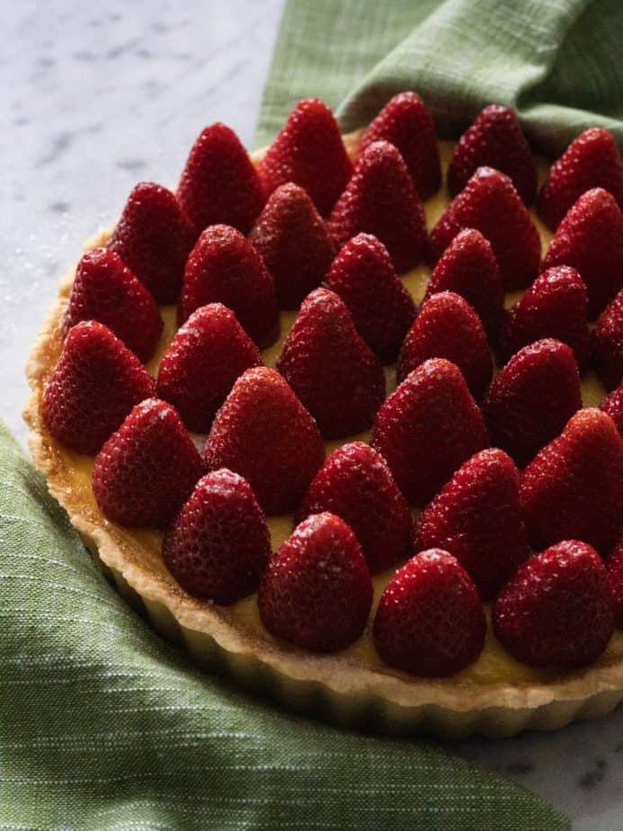 Side profile of a strawberry custard tart with a green cloth napkin on a marble countertop.