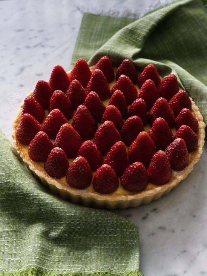 A strawberry custard tart with a green cloth napkin on a marble countertop.