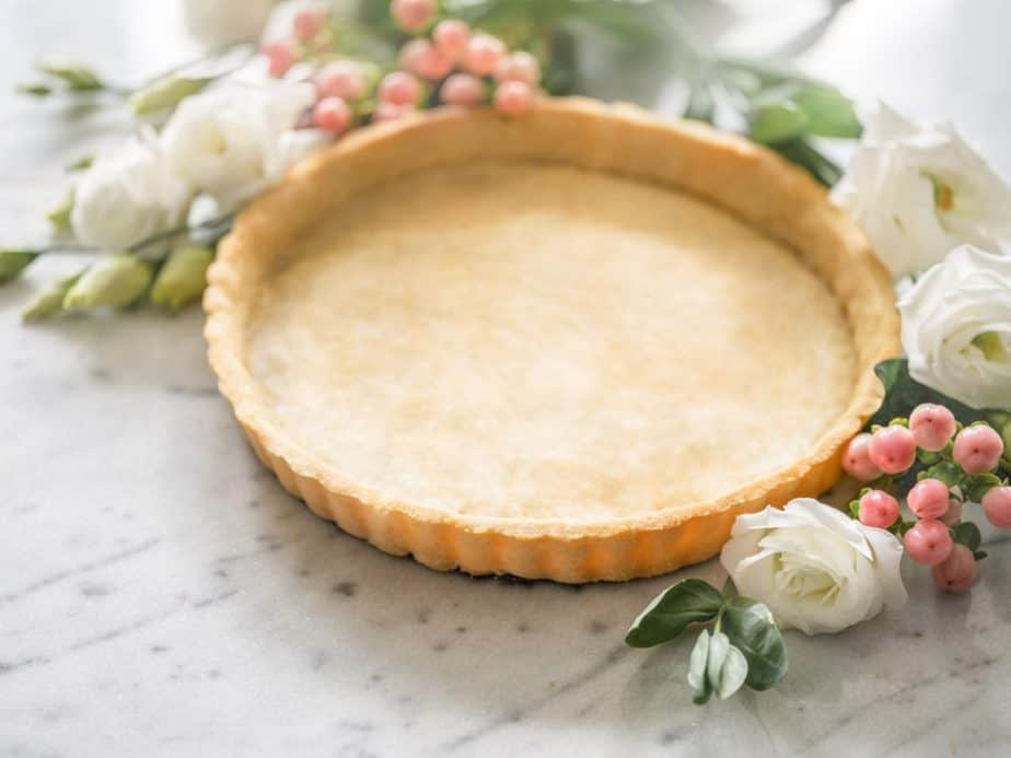 A tart crust on a marble countertop with flowers and berries.