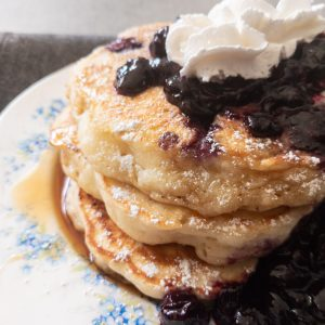 A stack of blueberry and whipped cream covered pancakes on a blue flower decorated plate.
