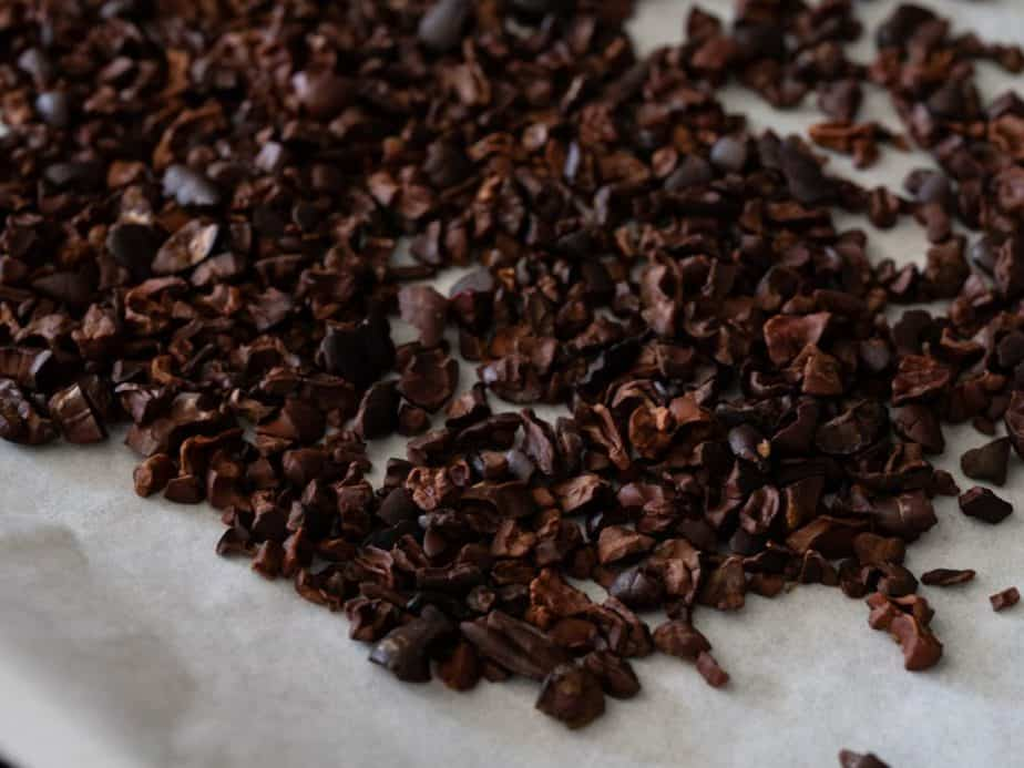 Roasted cacao nibs on parchment paper.