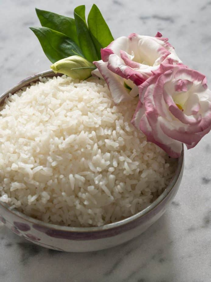 A bowl of Thai coconut rice with flowers.