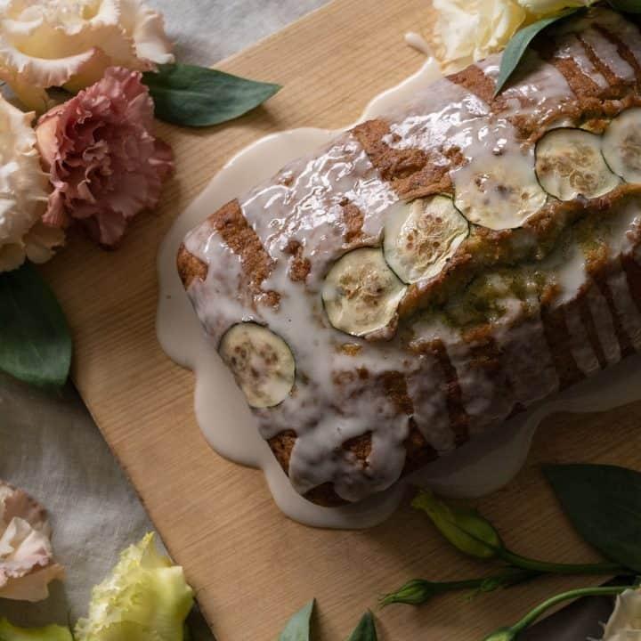 Glazed lemon zucchini bread with flowers on a grey cloth.