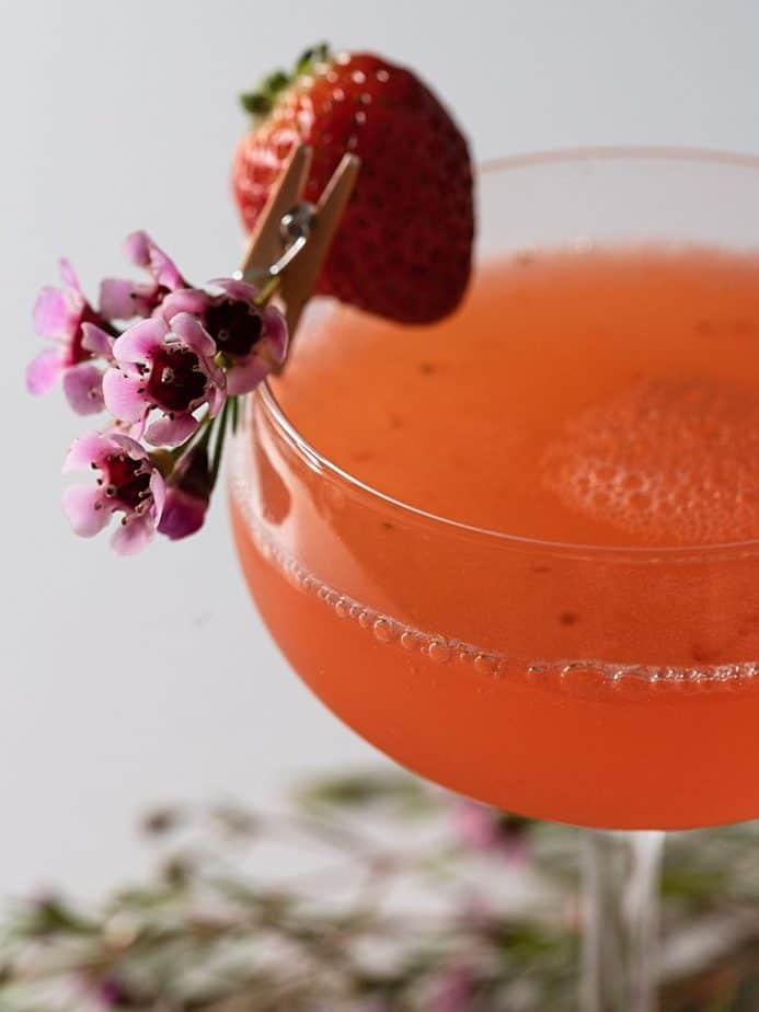 Closeup of the strawberry and flower garnish on the cocktail glass.
