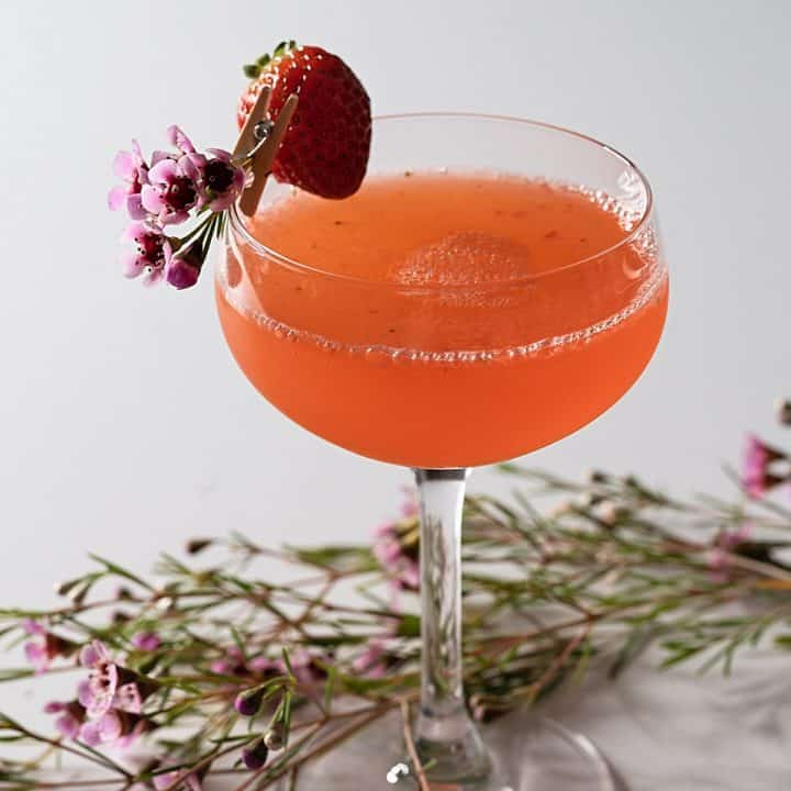 A muddled mission cocktail garnished with a strawberry and pink flowers.